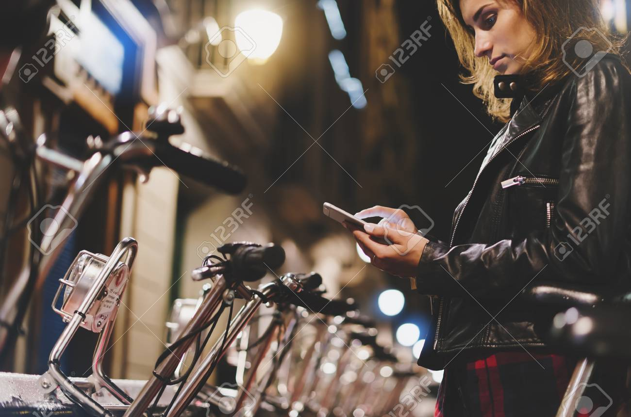 Young girl in black leather jacket using in hands screen smartphone