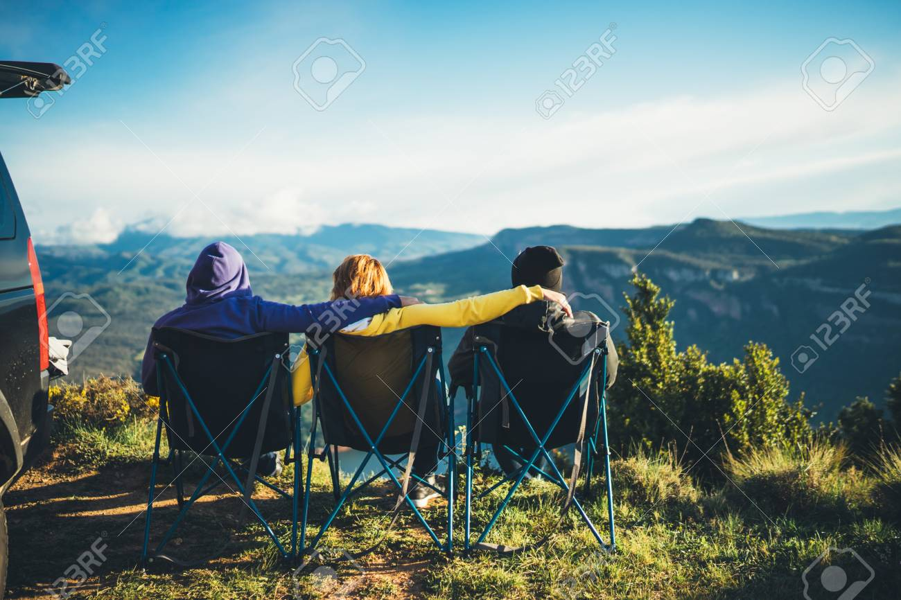 three friends sit in camping chairs on top of a mountain, travelers enjoy nature and cuddle, tourists look into distance on background of panoramic landscape, weekend concept - 120695665
