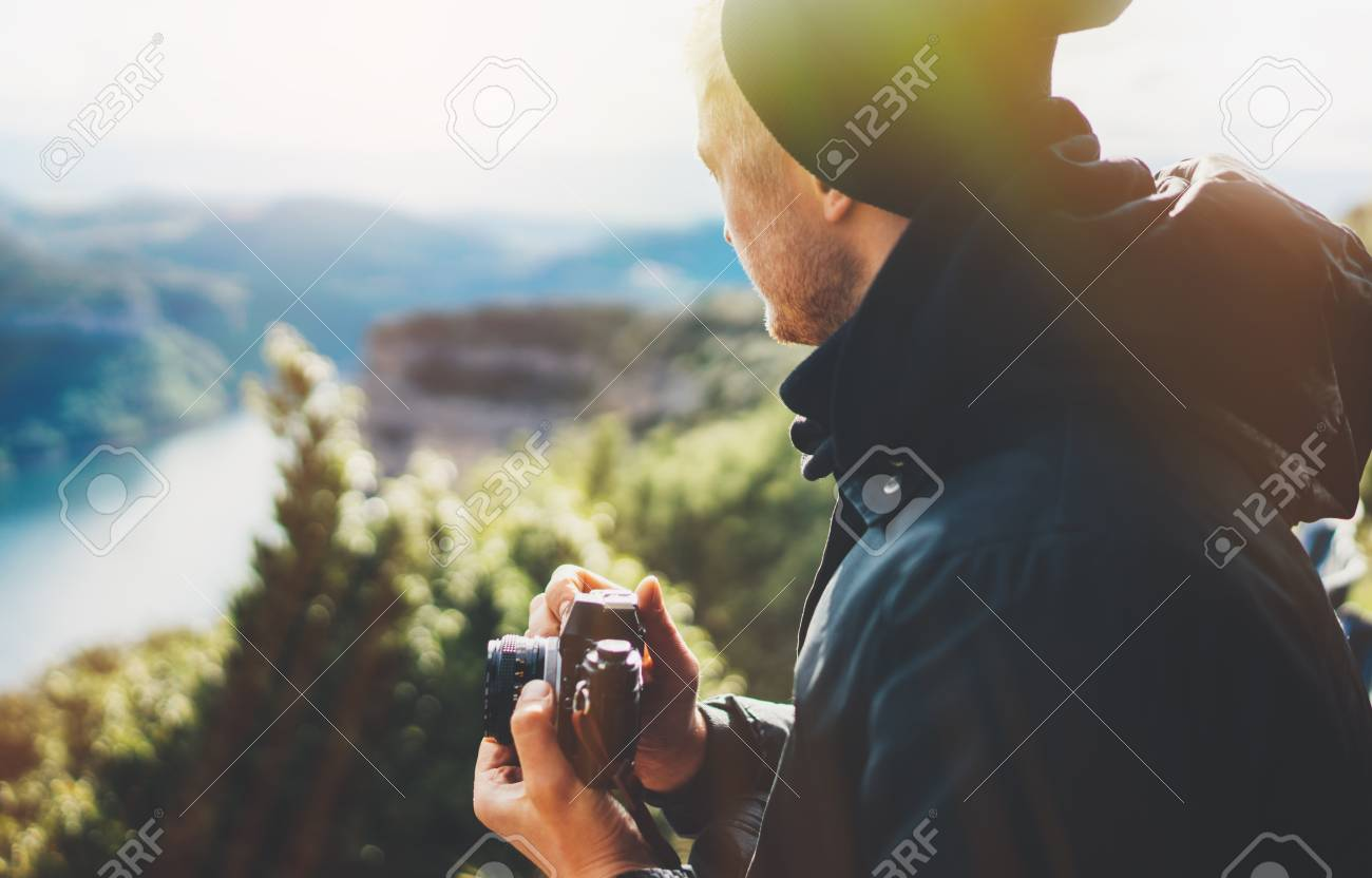 hipster tourist hold in hands taking photography click on retro vintage photo camera in auto, photographer looking on camera technology, hobby content, sun flare mountain, panoramic landscape vacation concept - 121168059