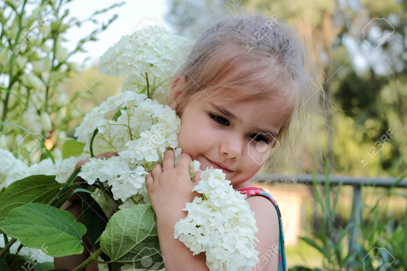 Beautiful blond little girl smelling big white flowers on the beautiful blond little girl smelling big white flowers on the bush outdoor portrait stock photo mightylinksfo Image collections