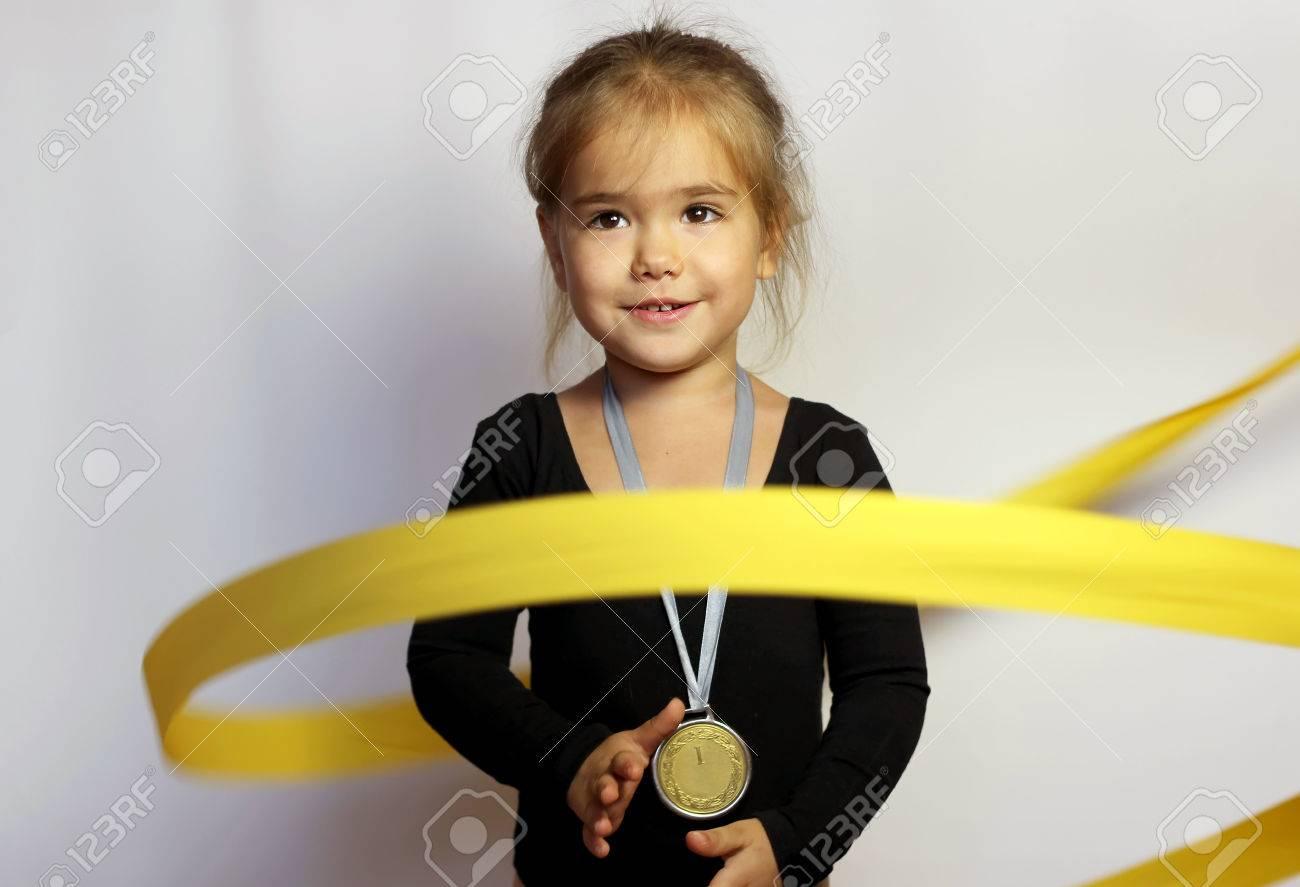 d510c5b4868 Jolie Petite Fille En Tenue De Sport Noir Avec Ruban Jaune Avec La Médaille  D or à Son Cou Sur Fond Blanc