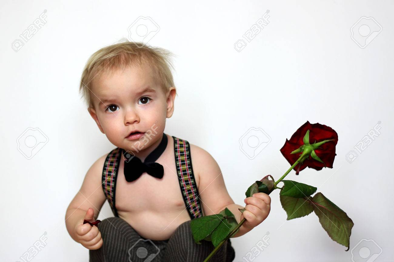 112338c4304 Little boy in suspenders and black bow-tie squatted and holding a red rose