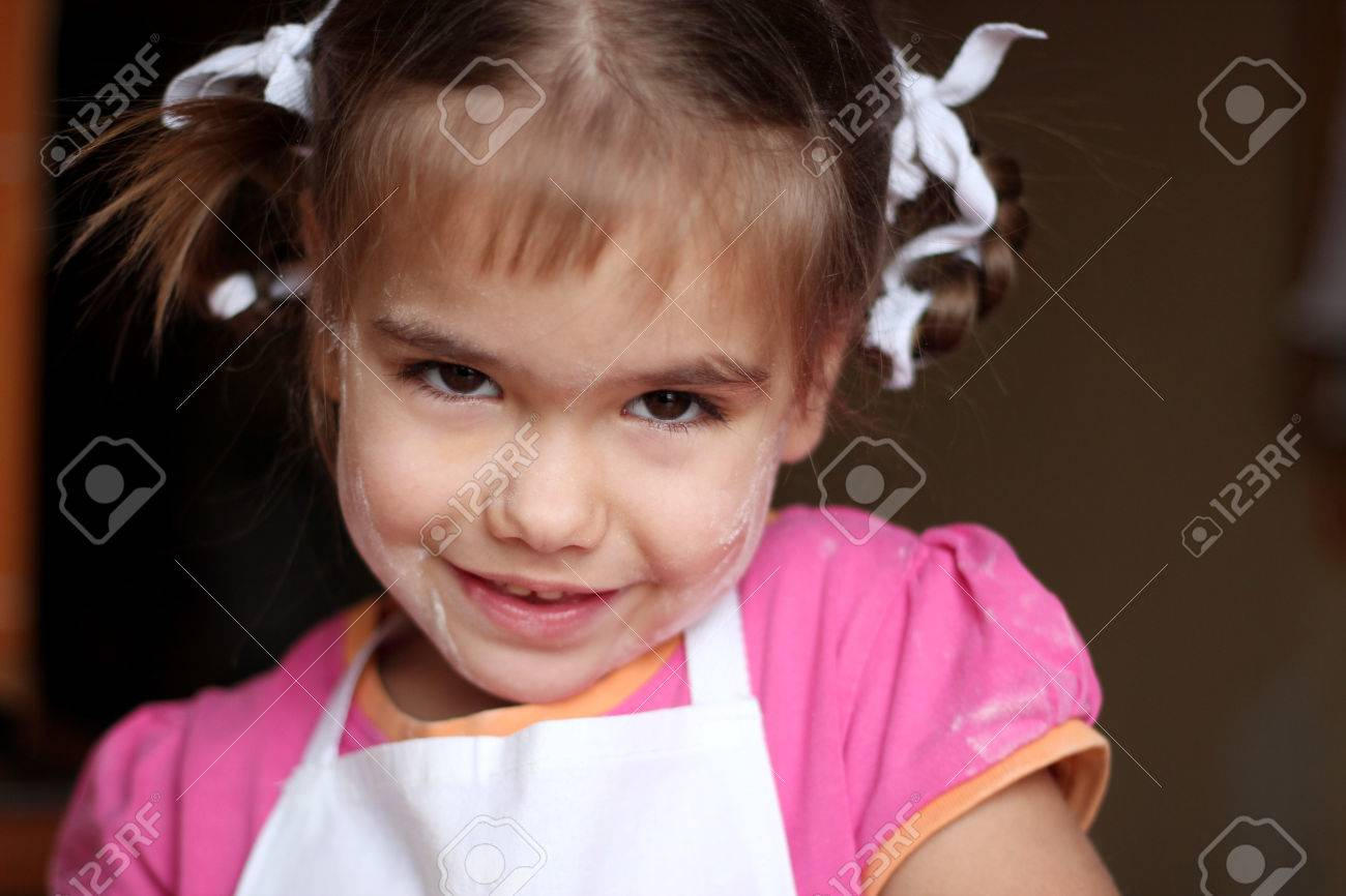 White apron girl - Portrait Of Pretty Little Girl In White Apron Smiling After Baking Cookies By Herself Face