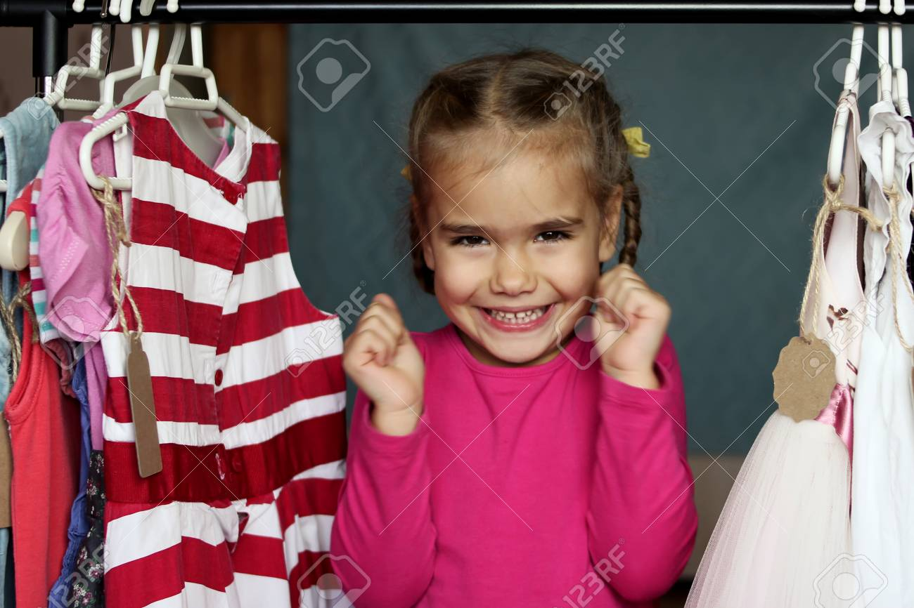 d7b363c08 Cute preschooler girl hugging chosen new lovely dress among a lot of clothes  in child fashion store; she is happy. Sale, gifts, Christmas, holidays; ...