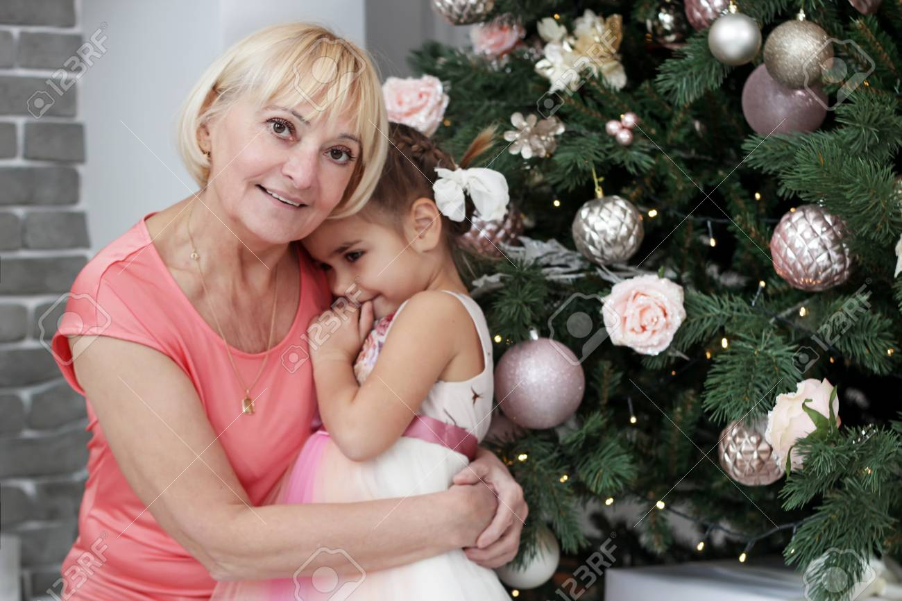 Portrait Of Happy Grandmother Hugging Her Granddaughter Over Christmas Presents And Decorated New Year Tree