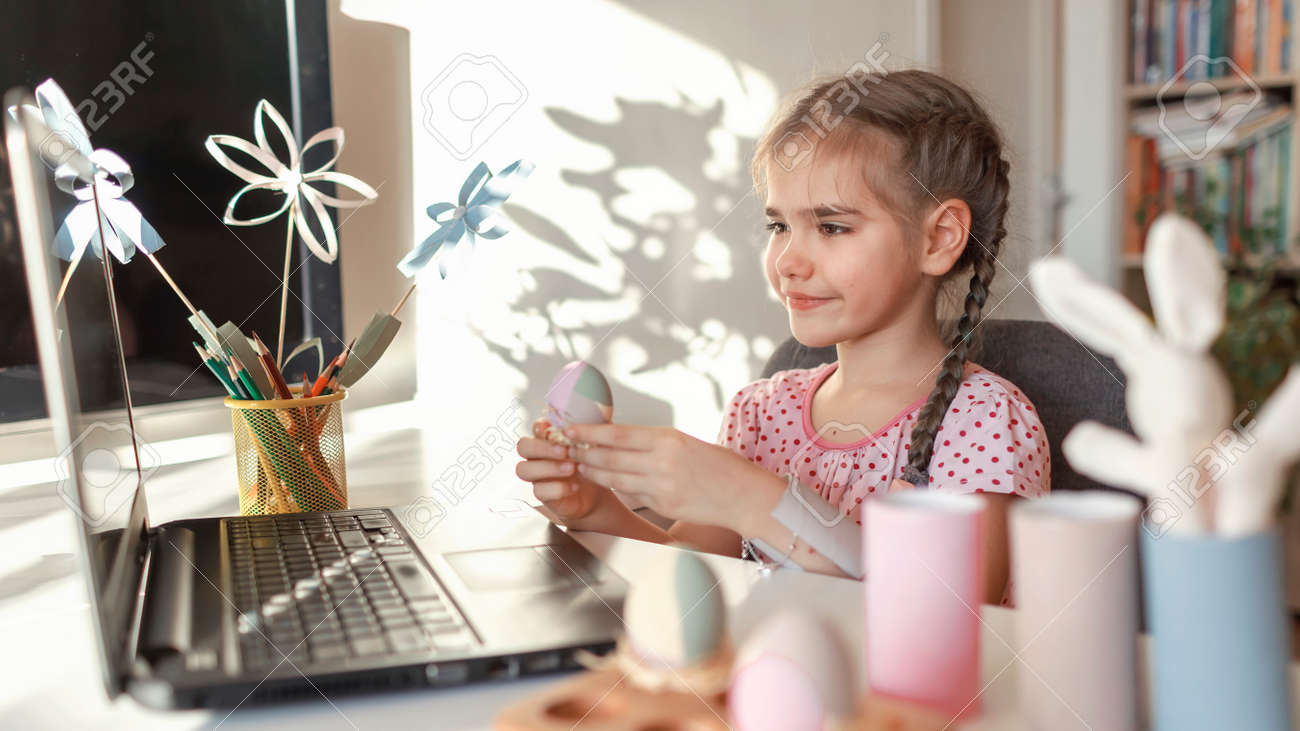 Girl demonstrating DIY flowers, wreath, eggs and greeting with spring holidays her family via internet, online Eater celebration, zero waste, craft for kids, new normal and social distance - 165694901