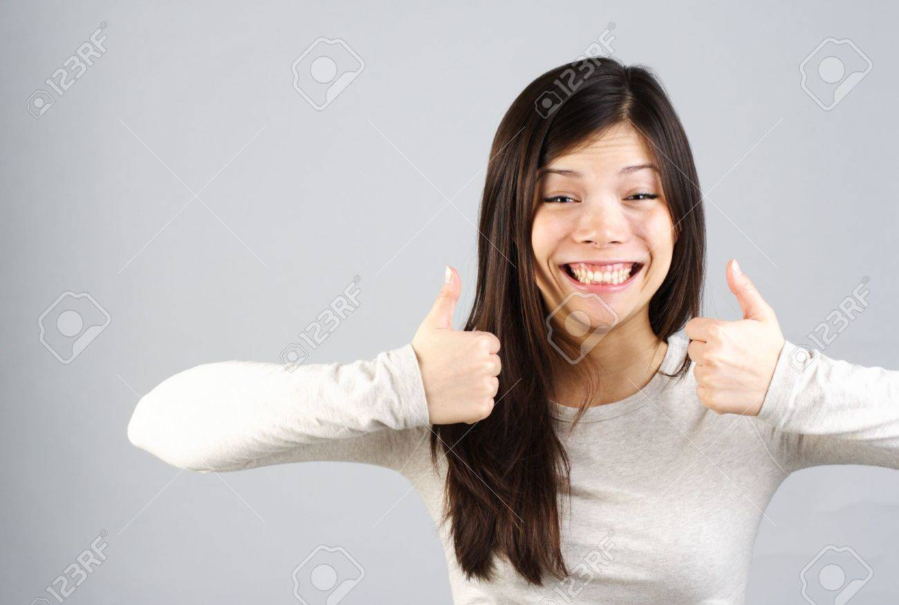 Pretty young woman giving two thumbs up with funny expression Stock Photo - 4469502