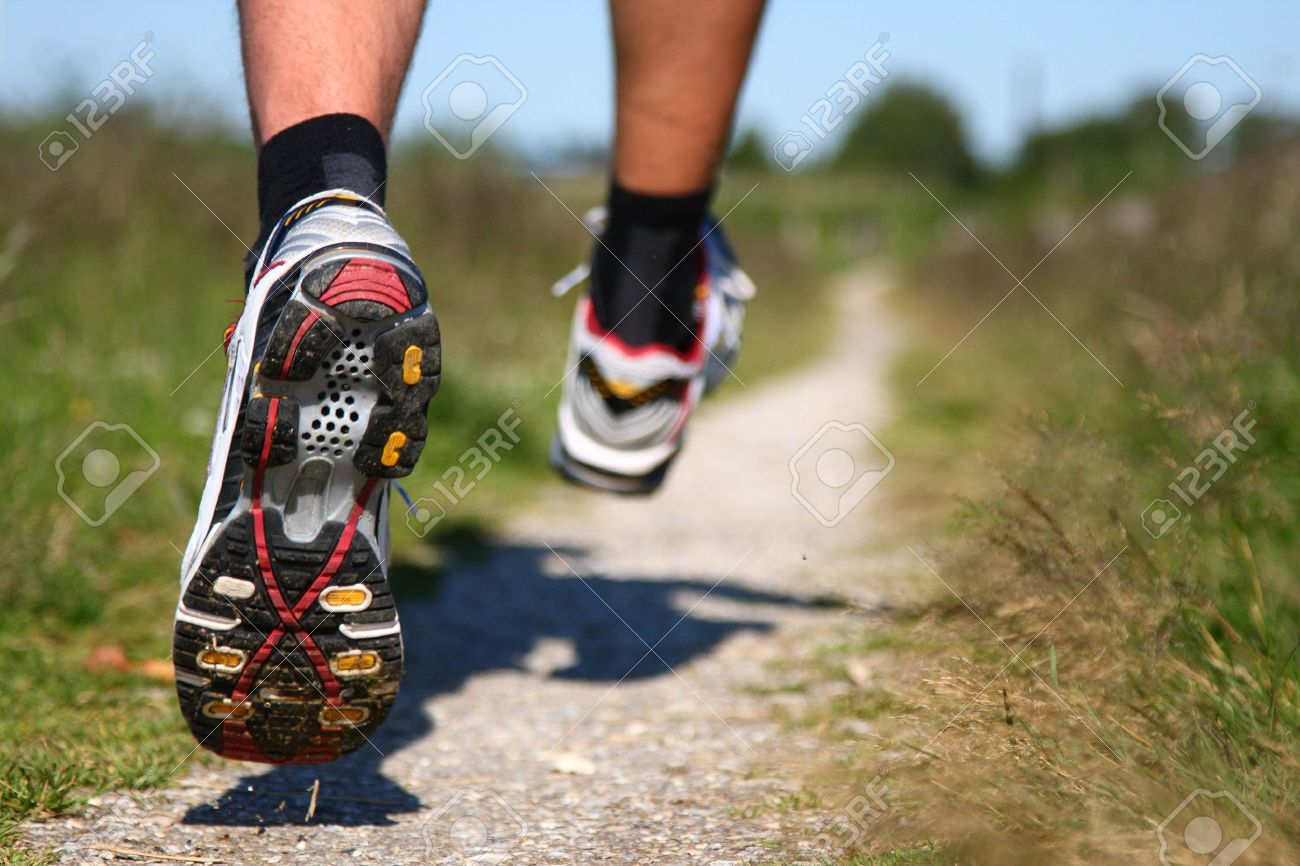 Trail running. Freeze action closeup of running shoes in action. Shallow depth of field, focus on left shoe. - 5117272