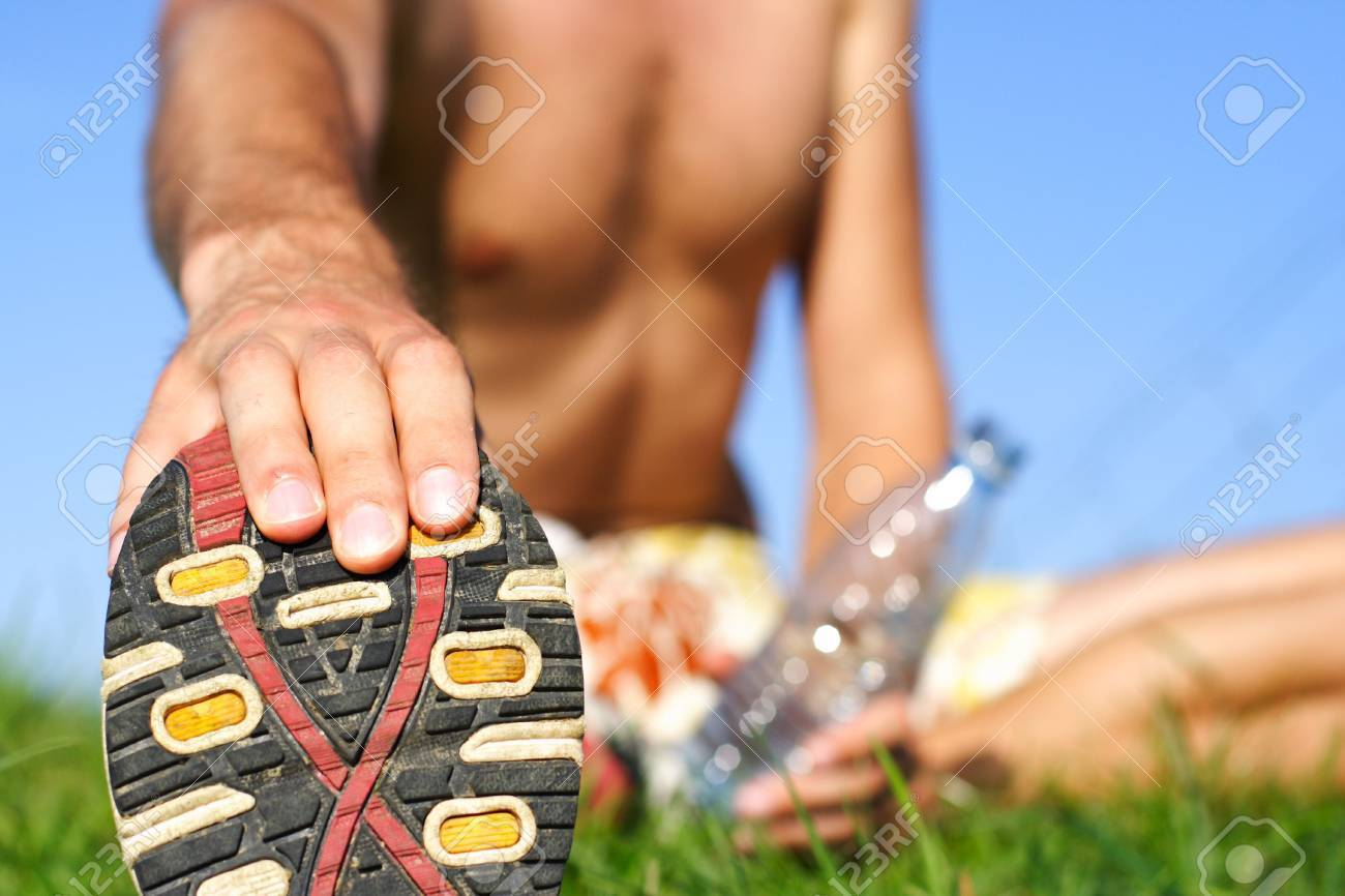 Man stretching out after running outdoors a summer night in Denmark. Shallow depth of field, focus on the shoe. Stock Photo - 5316066