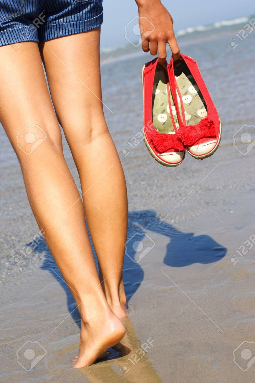 woman walking on the beach holding her shoes Stock Photo - 5422777