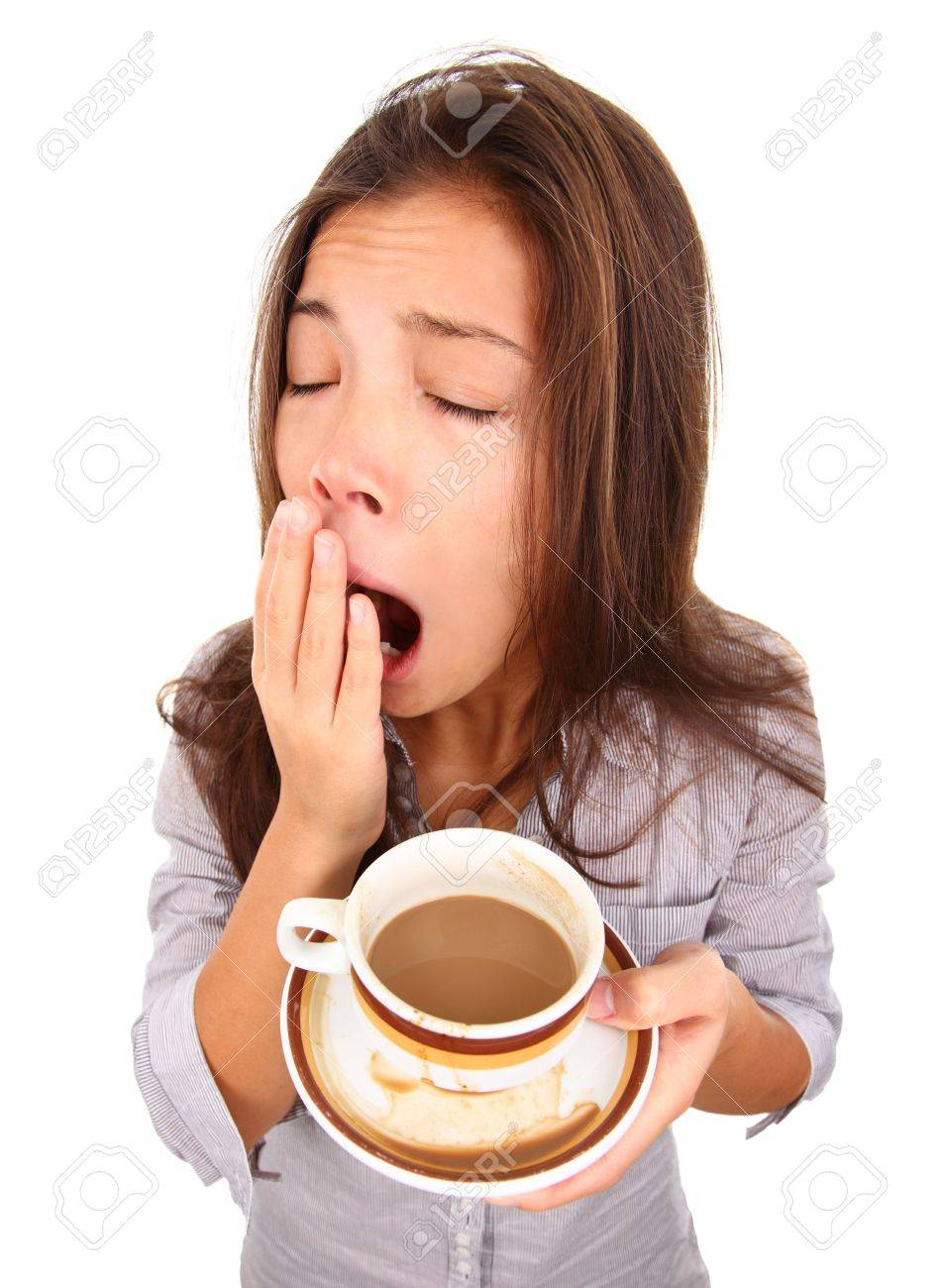 Tired woman yawning spilled a little coffe. Beautiful mixed race asian / caucasian model isolated on white background. Stock Photo - 6035269