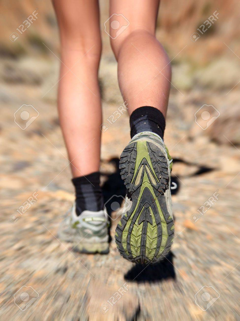 Woman running on trail in desert. Zoom motion blurred closeup shoes of woman trail running in desert. Stock Photo - 6825828