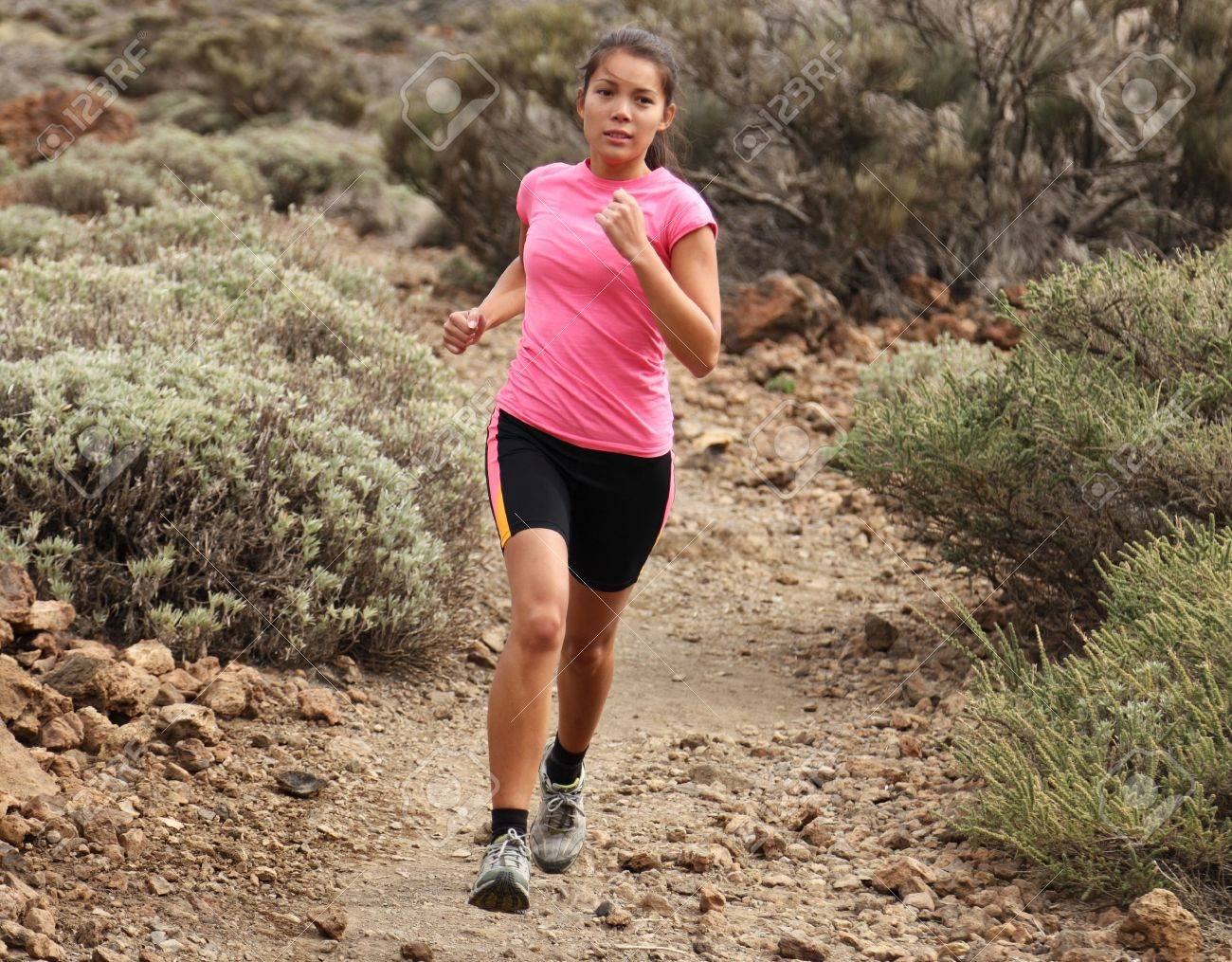 Woman running. Woman trail running outdoors on dirt single track in desert landscape in cross country running shoes. Stock Photo - 6878844