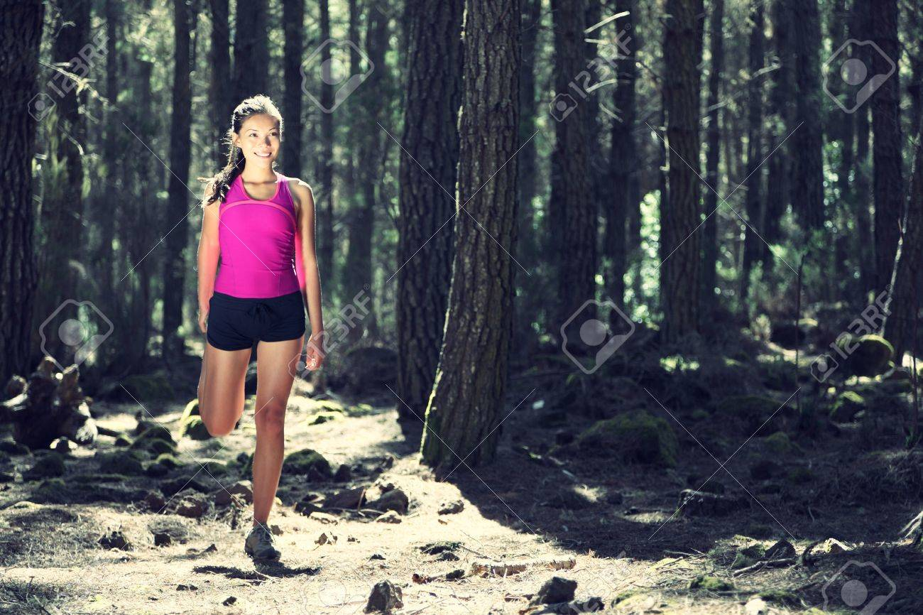 Runner stretching out during running. Beautiful young woman athlete. Caucasian / Asian female model Stock Photo - 7755976
