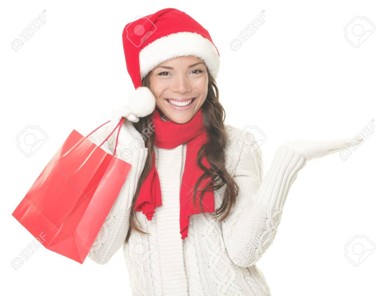 Christmas shopping woman presenting copy space. Excited santa girl showing your product or text looking sideways on copyspace with open hand palm. Closeup of mixed Asian Caucasian female model isolated on white background. Stock Photo - 8049696