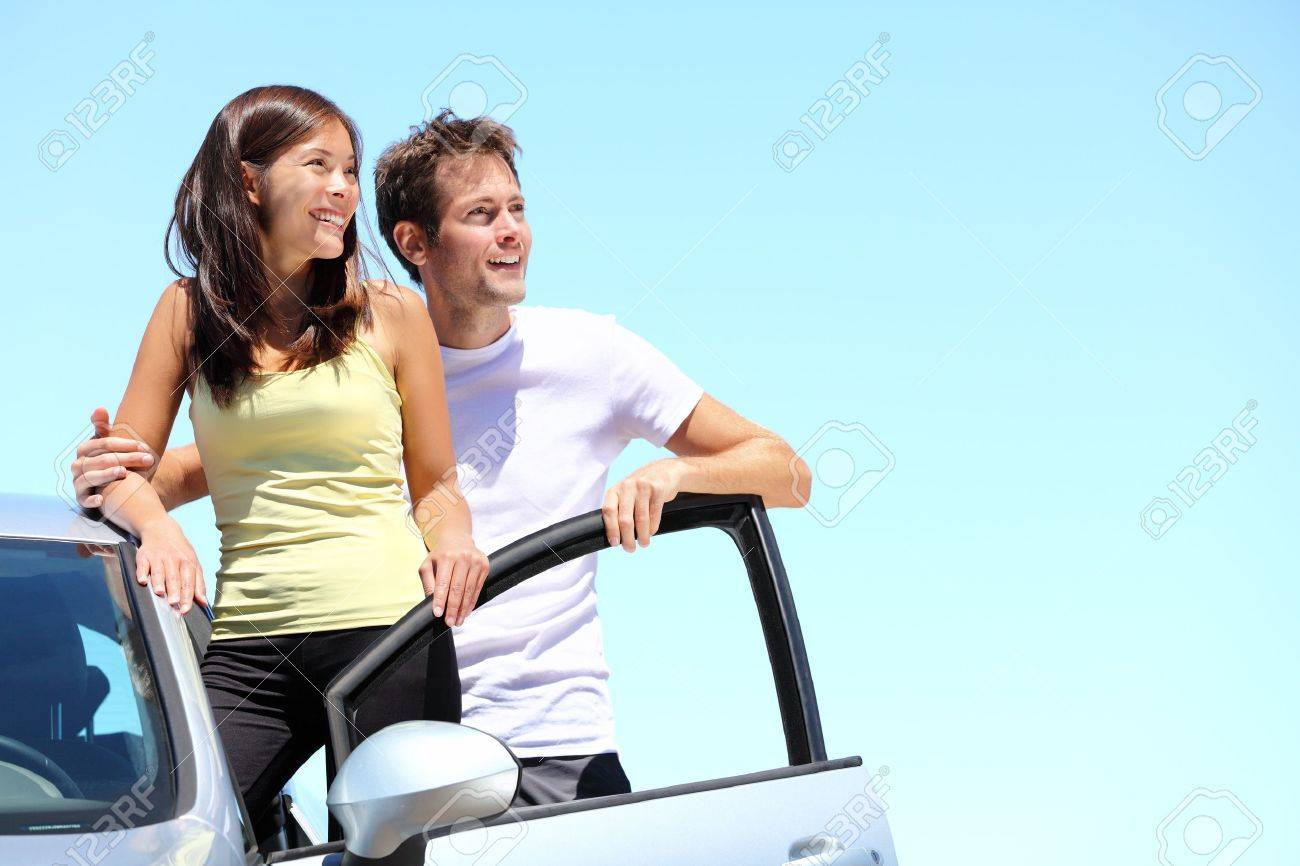 Happy couple with car. Young interracial couple standing with car looking at the sky with copy space. Stock Photo - 9466349