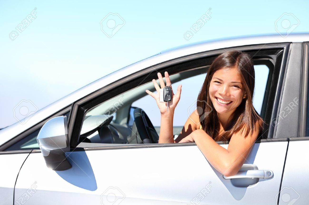 Asian car driver woman smiling showing new car keys and car. Mixed-race Asian and Caucasian girl. Stock Photo - 9981818