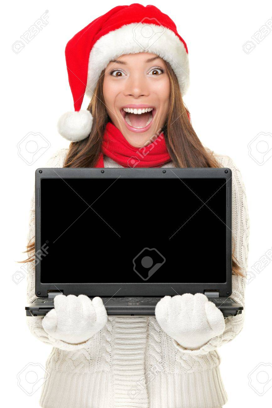 Christmas computer woman holding notebook excited wearing santa hat. Empty blank screen copy space for text. Beautiful young smiling female model isolated on white background. Stock Photo - 10704089