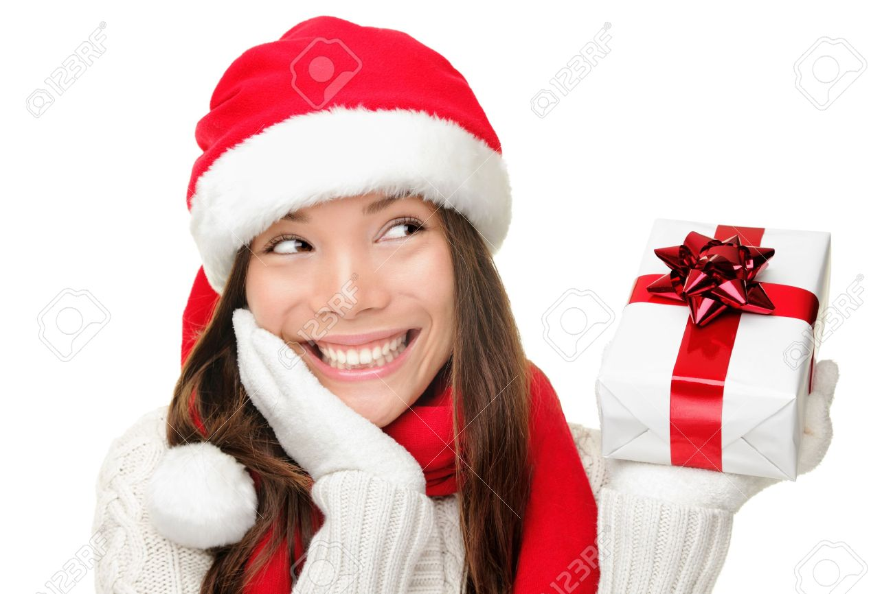 santa girl holding christmas gift young happy woman in santa hat looking sideways showing christmas