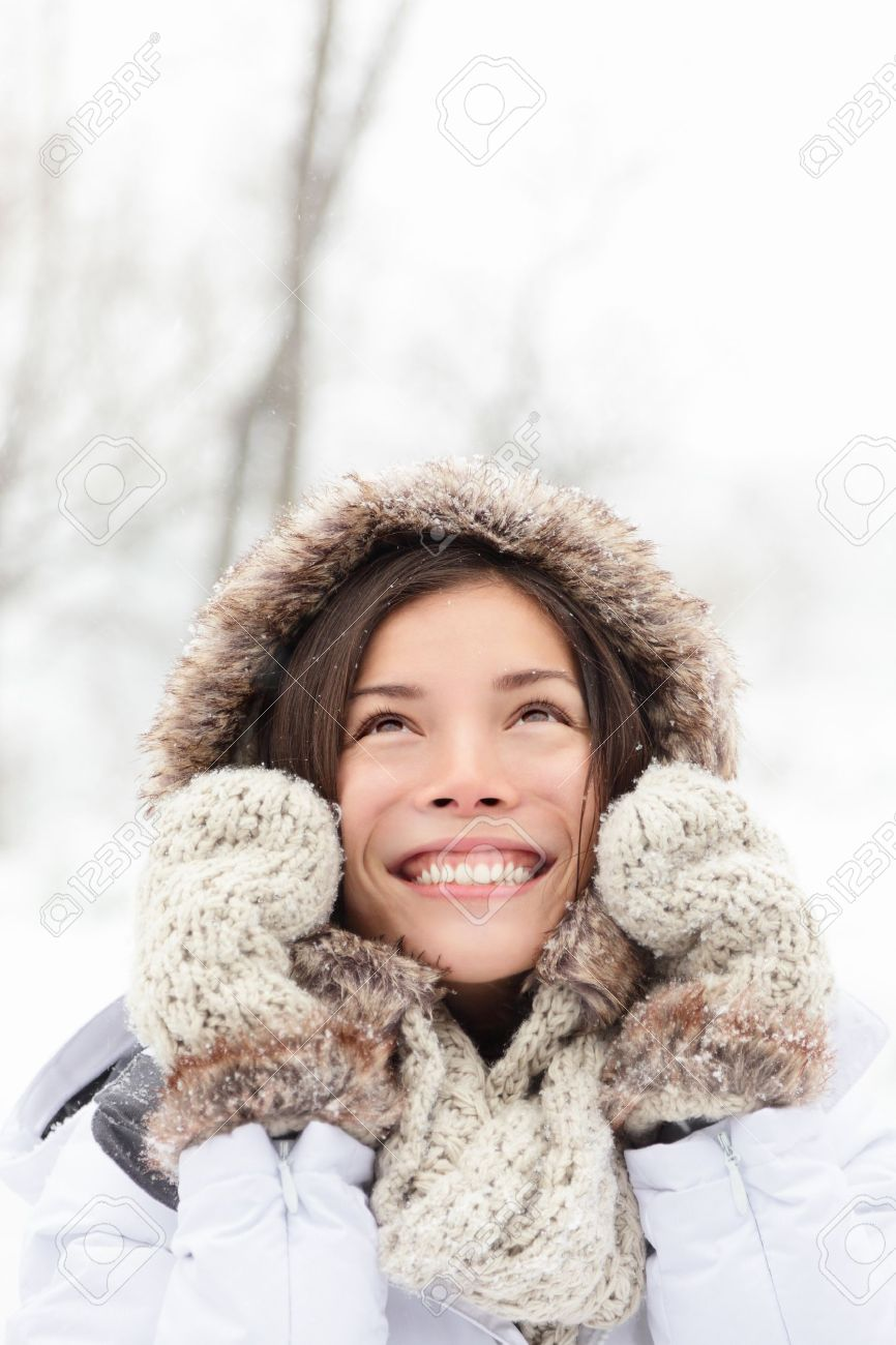 winter woman in snow looking up at copy space outside on snowing cold winter day. Portrait multiethnic Caucasian Asian female model outside in first snow Stock Photo - 11404504
