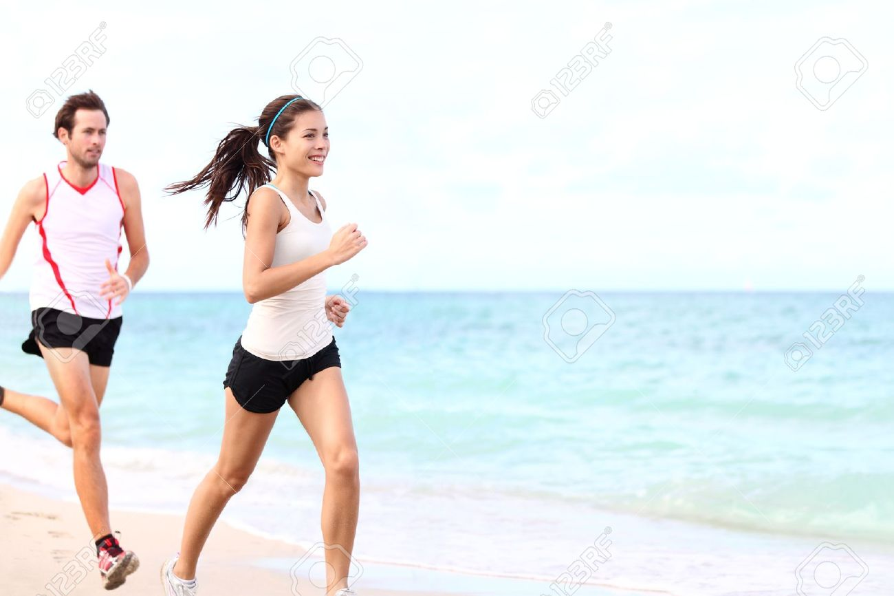 sport - couple running on beach traing for marathon run. Young multiracial couple runners, smiling asian female fitness model and caucasian male model. Stock Photo - 11841051