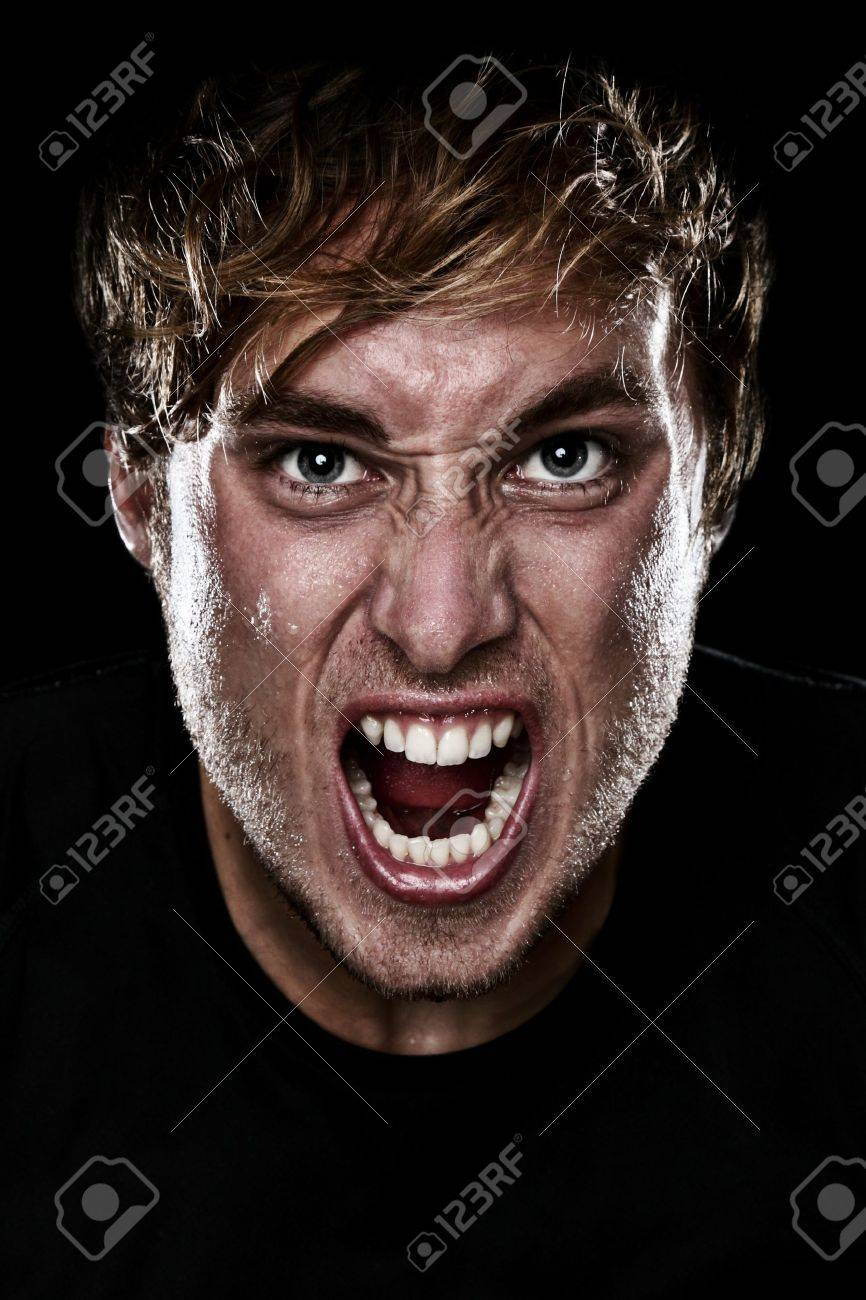 Man screaming angry aggressive at camera on black background. Young Caucasian mad male model. Stock Photo - 12019141