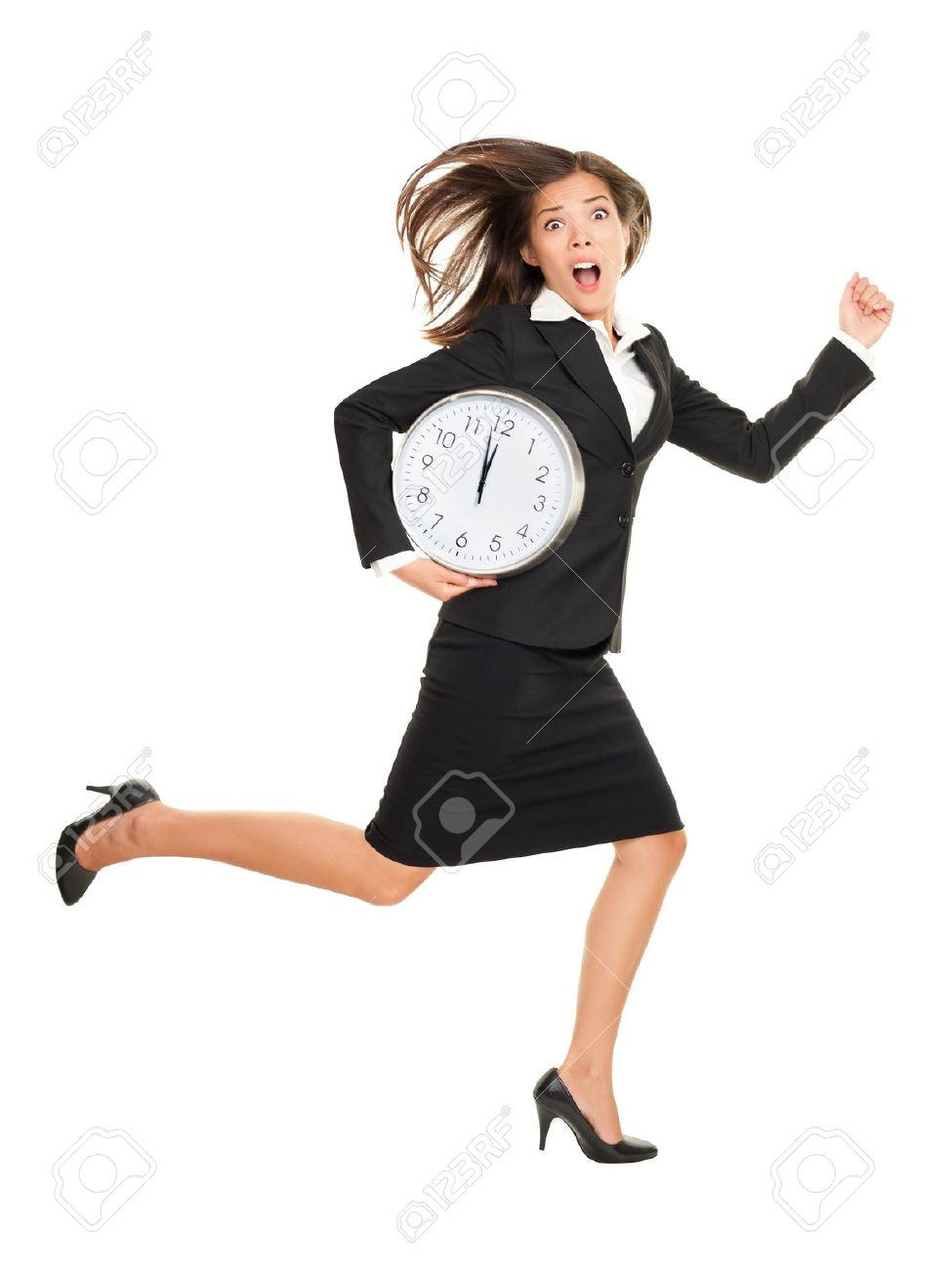 Stress - business woman running late with clock under her arm. Business concept photo with young businesswoman in a hurry running against time. Caucasian / Chinese Asian isolated on white background in full length. Stock Photo - 12288404