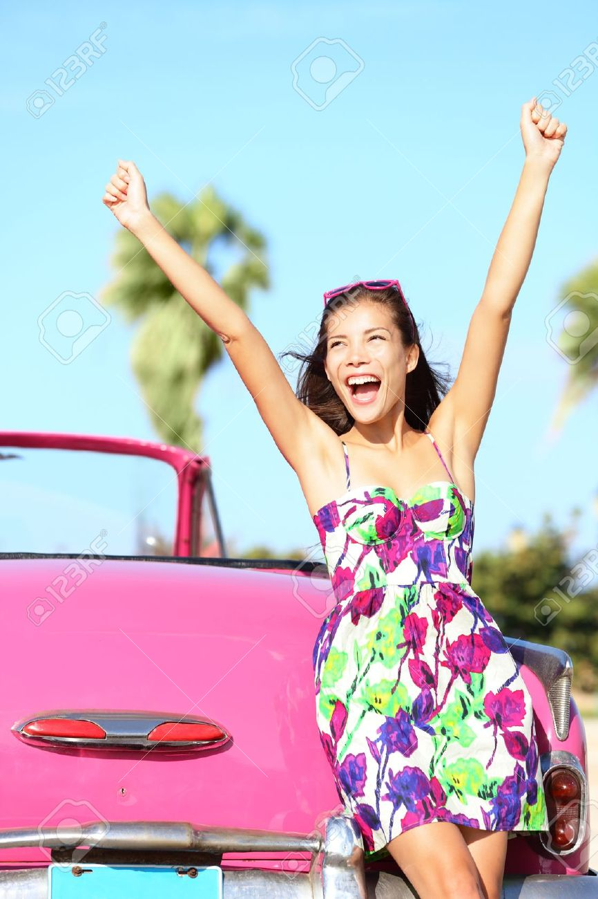 Summer vacation car road trip freedom concept. Happy woman cheering joyful in summer dress during holiday travel in pink vintage car. Beautiful young mixed race Caucasian / Chinese Asian female model in Havana, Cuba. Stock Photo - 12288420
