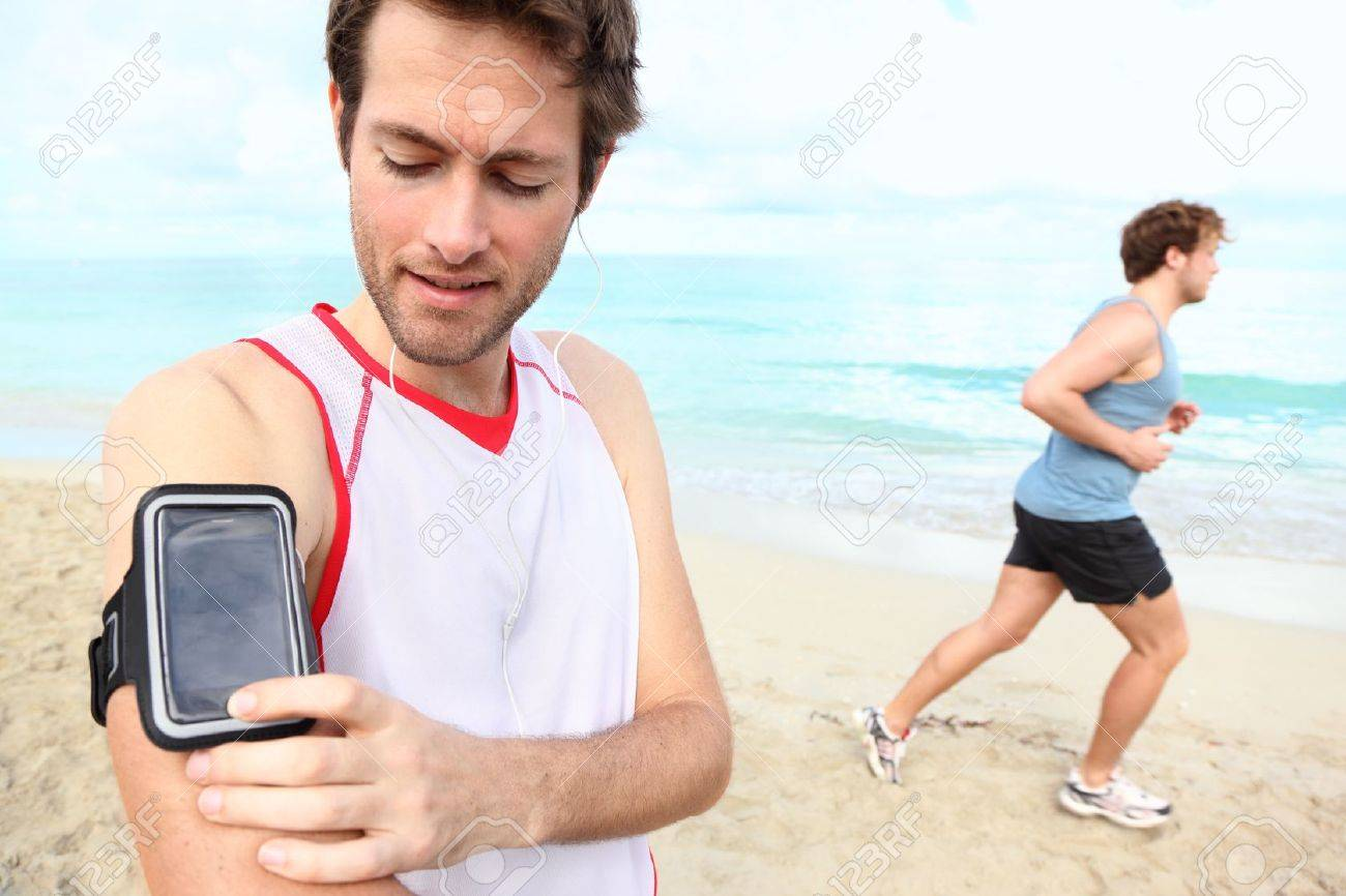 Running workout man with mp3 music player listening to music with mp3 player armband or smart mobile phone. Stock Photo - 12288484