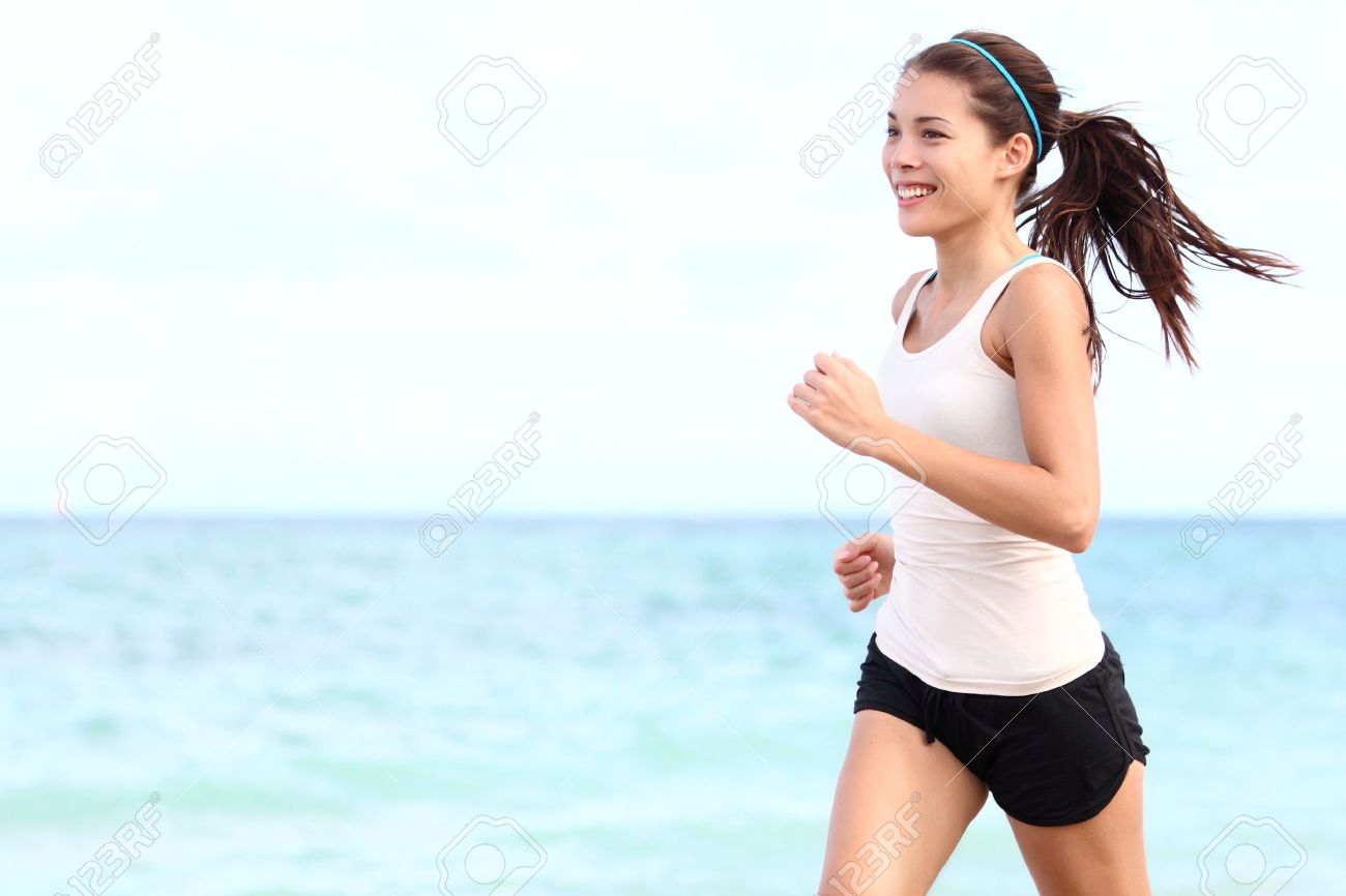 Running woman. Female runner jogging during outdoor workout on beach. Beautiful fit mixed race Fitness model outdoors. Stock Photo - 12288468