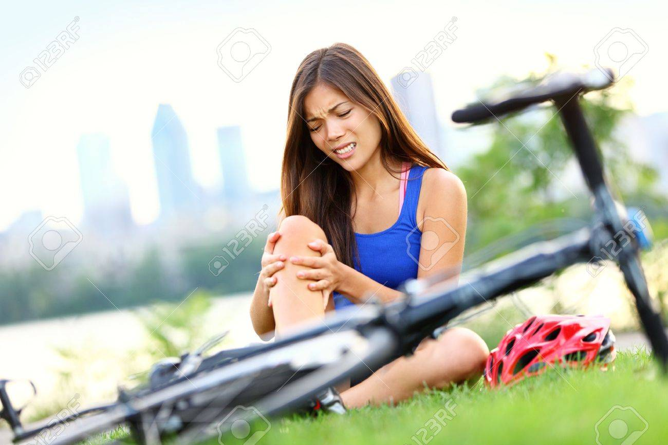 Knee pain bike injury. Woman with pain in knee joints after biking on bicycle. Girl sitting down with painful face expression. Mixed race sport fitness model outdoors. Stock Photo - 12611629