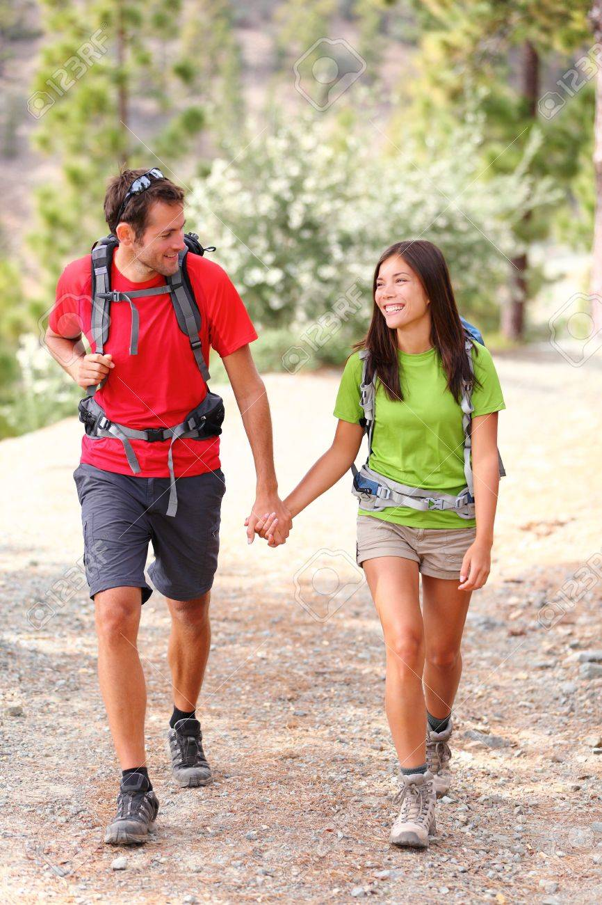Young hikers smiling happy holding hands walking in forest during camping travel. Stock Photo - 12720585