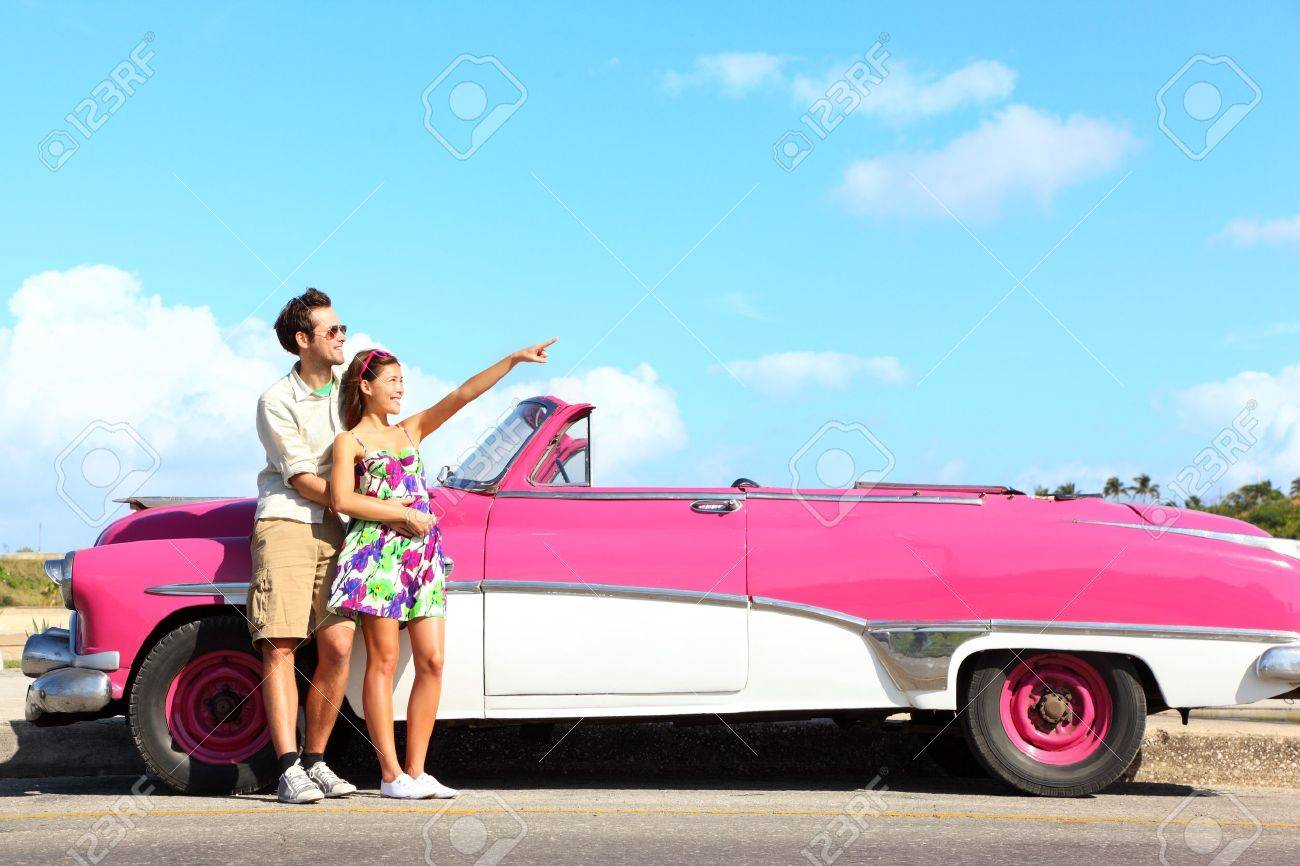 Vintage car  Couple pointing looking standing by pink retro vintage car smiling happy  Young couple on summer road trip car holiday in Havana, Cuba  Asian woman, Caucasian man Stock Photo - 13044797