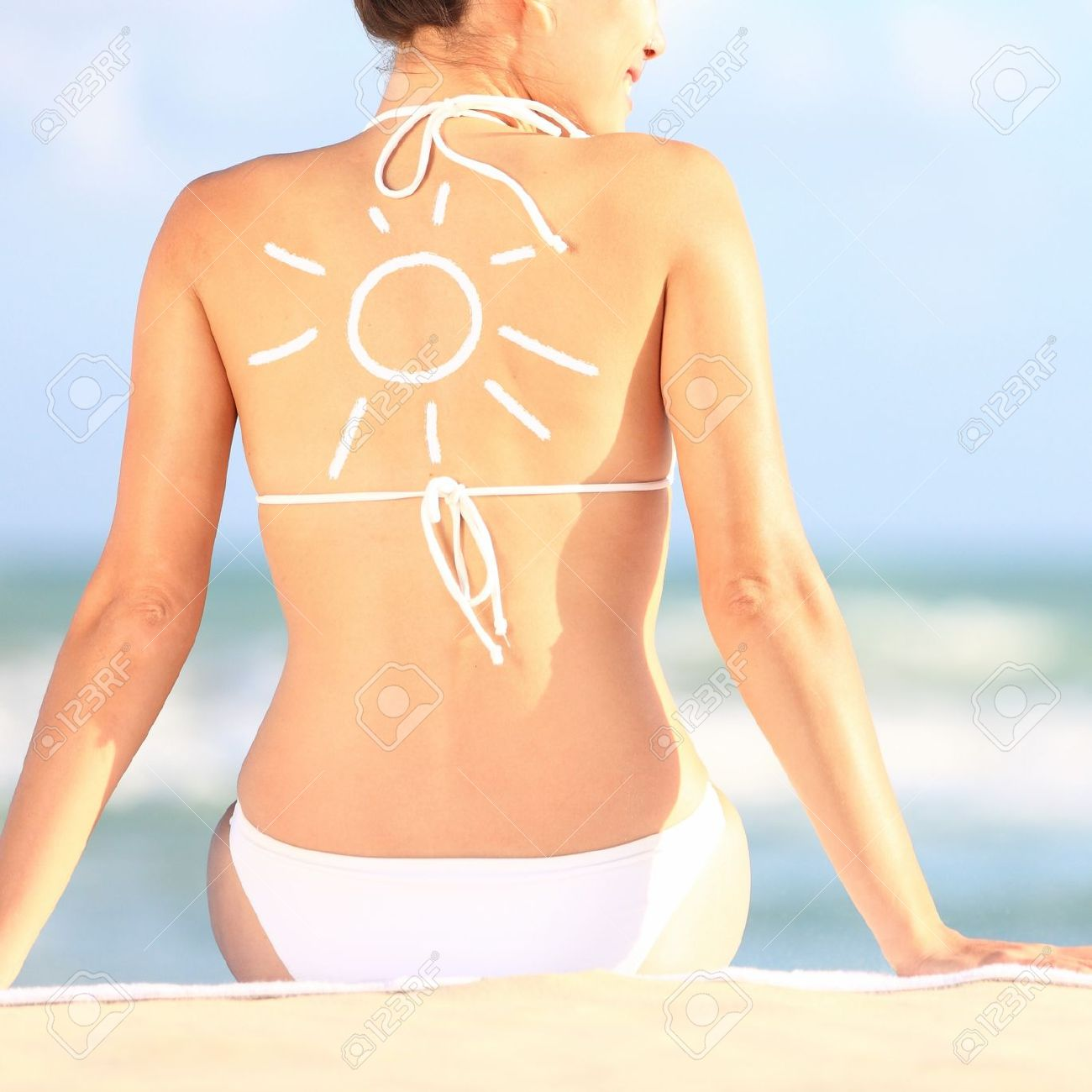 Sunscreen   sun tan lotion sun drawing on woman back  Girl in bikini sitting on beach in sunlight Stock Photo - 13120121