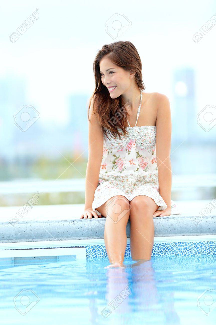 Pool woman relaxing sitting in summer dress with legs in pool smiling happy with skyline in background  Beautiful mixed race Asian Chinese   Caucasian girl Stock Photo - 13281736