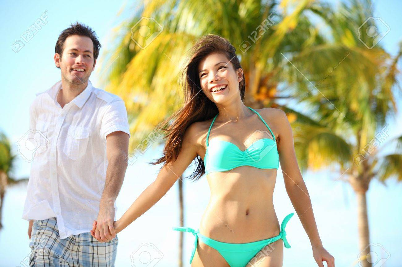 Couple having fun on beach. Happy young interracial couple running on beach during summer vacation on tropical resort. Asian woman, Caucasian man smiling happy in Varadero, Cuba Stock Photo - 13281744