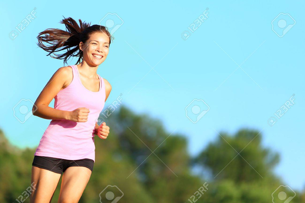 eabbdfd9fd54 Happy woman running in city park. Asian girl runner jogging smiling  aspirational outside on beautiful