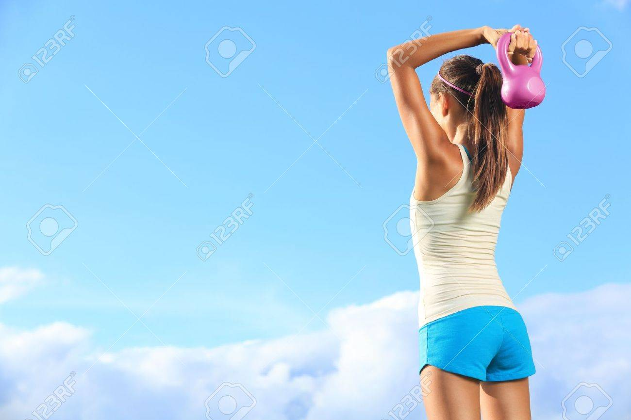 Fitness woman using kettlebells outside during crossfit strength training against copyspace. Stock Photo - 15589198