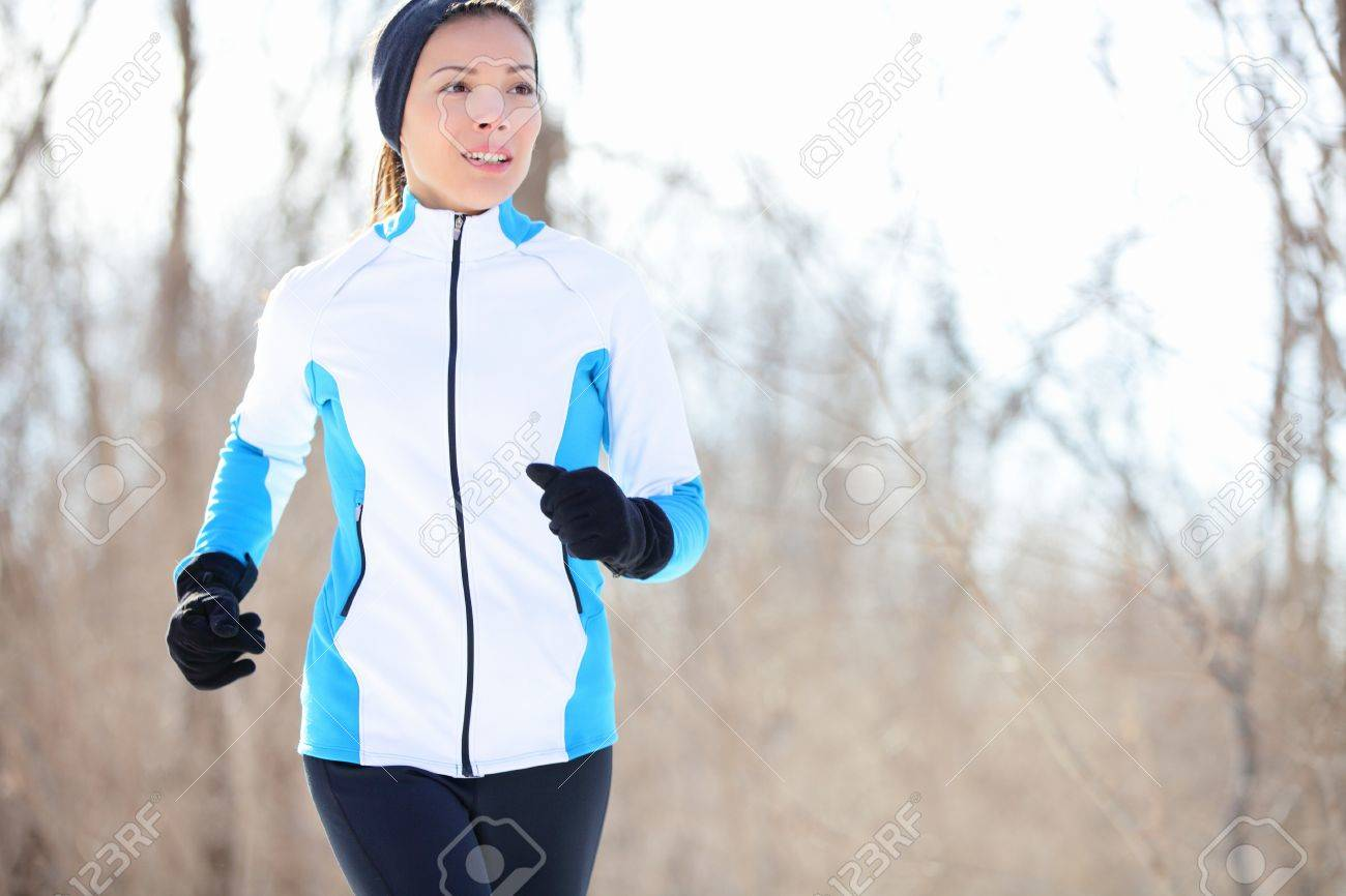 Running young Asian woman jogging in a winter fleece and gloves in open countryside with copyspace in a health and fitness concept Stock Photo - 15589190