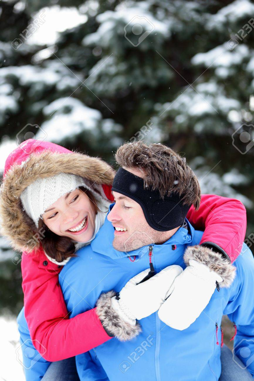 Happy winter couple having fun doing piggyback in snow winter landscape outside in forest  Beautiful young interracial couple piggybacking Stock Photo - 15720975