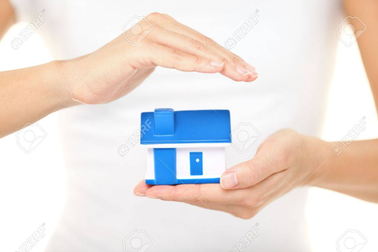 Home insurance  Woman holding a model house in one hand while forming a protective covering with the other conceptual of home insurance and protection Stock Photo - 16686424