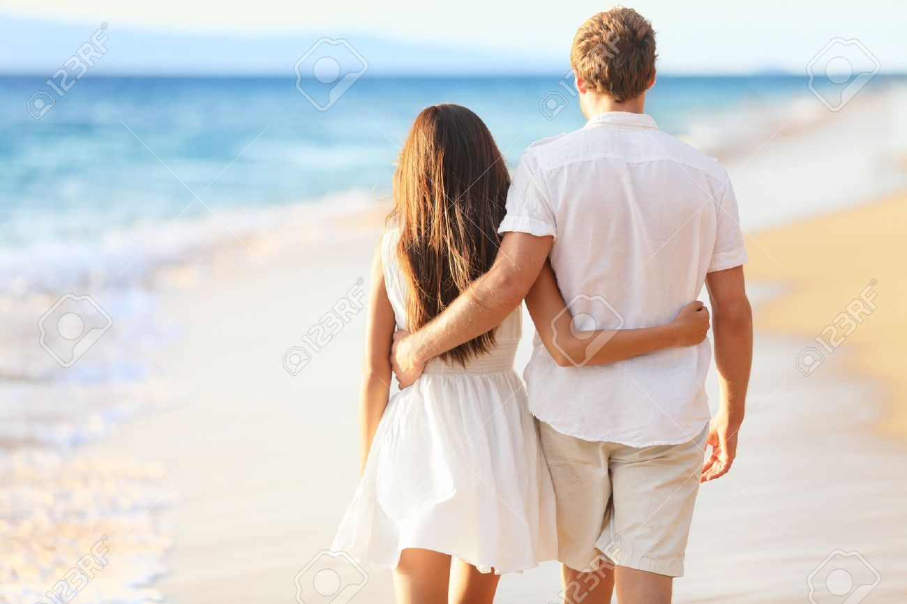 Vacation couple walking on beach together in love holding around each other. Happy interracial young couple, Asian woman and Caucasian man. Stock Photo - 17133525