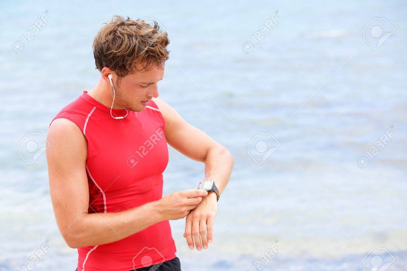 Athlete runner looking at heart rate monitor watch  Man running on beach taking a break in compression t-shirt top Stock Photo - 17417749