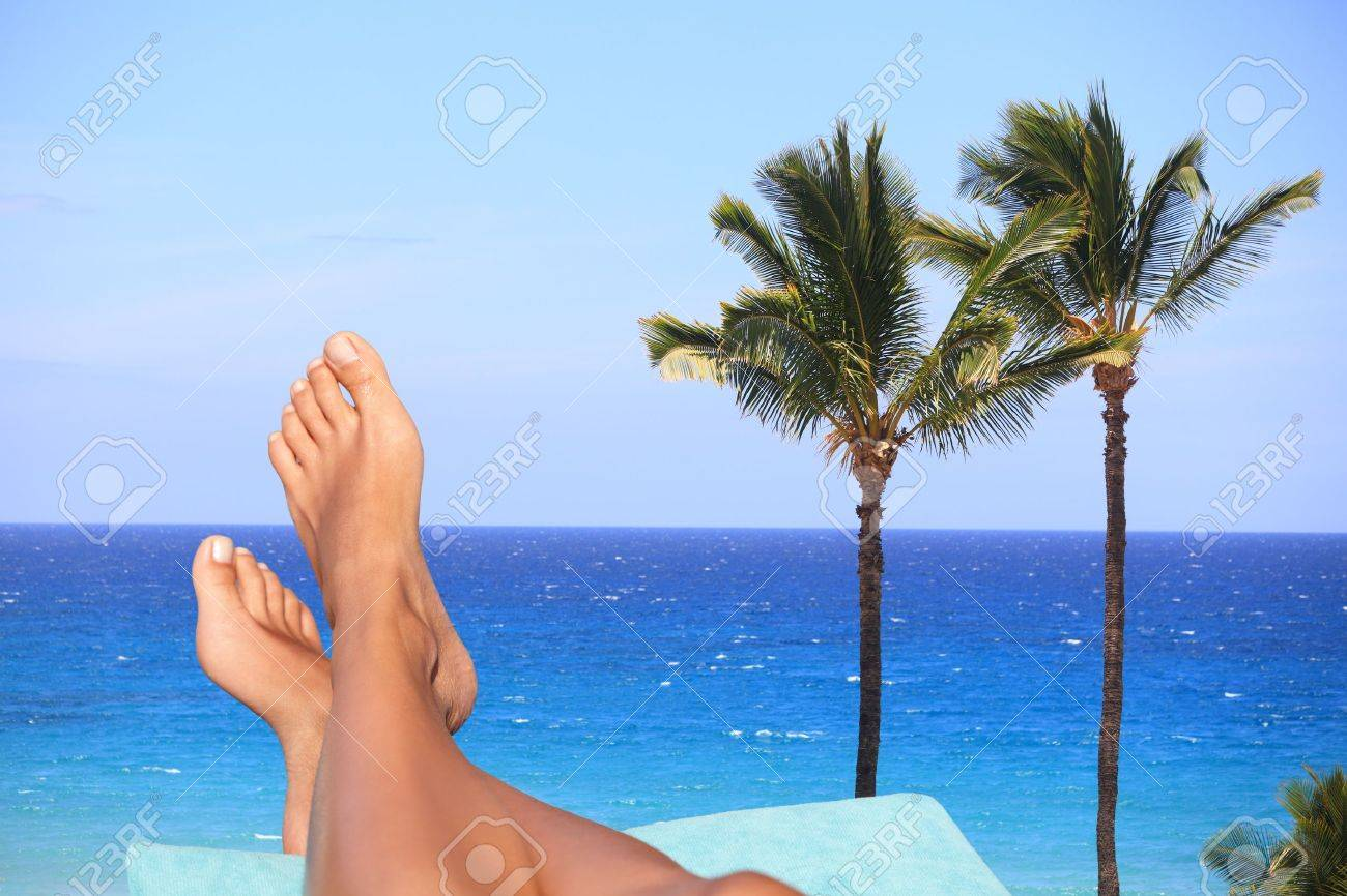 Bare female feet resting on a recliner overlooking a blue tropical ocean with palm trees conceptual of a summer vacation or travel Stock Photo - 17471004