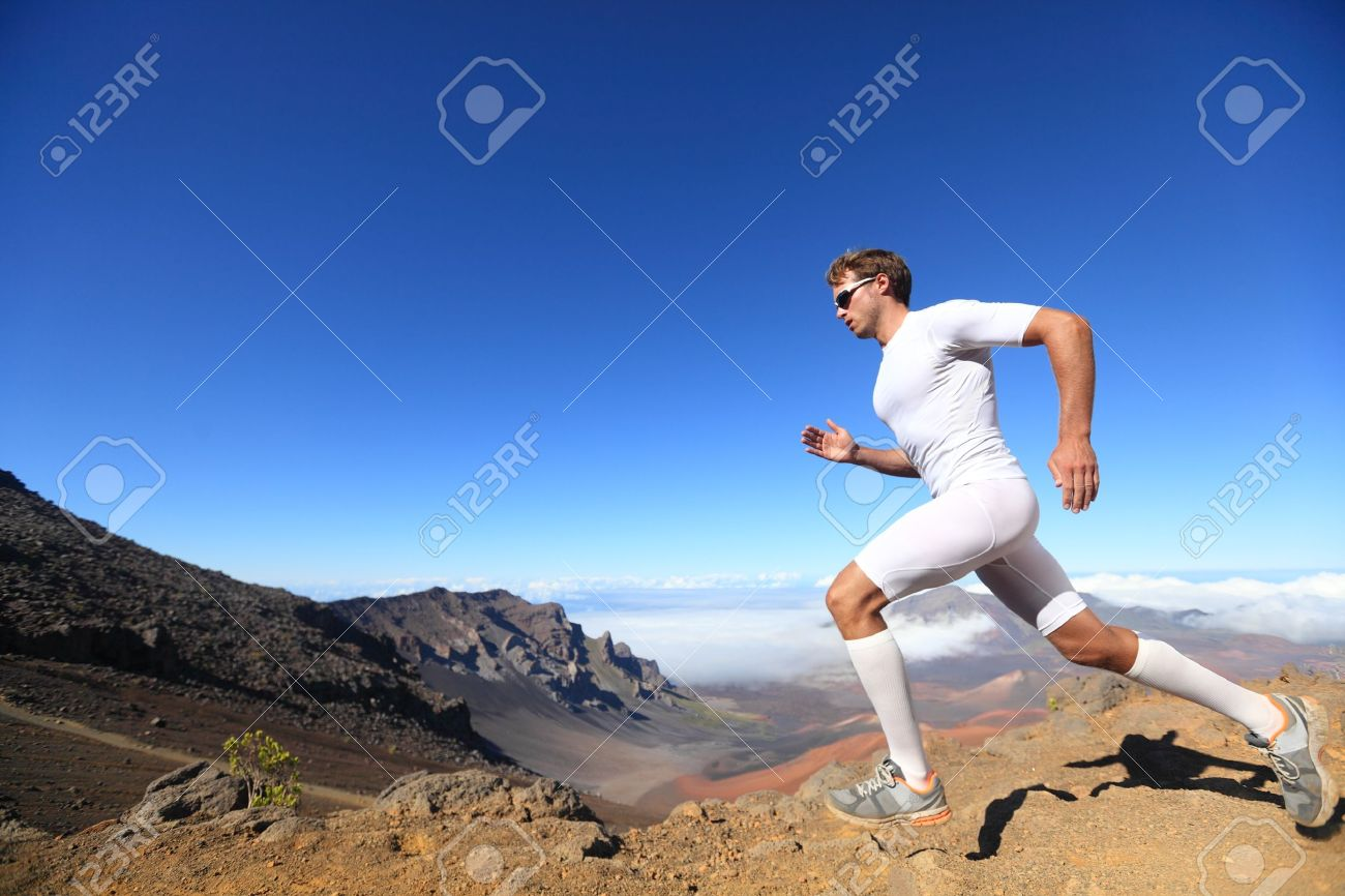 Running sport. Man runner sprinting outdoor in scenic nature. Fit muscular male athlete training trail running for marathon run. Sporty fit athletic man working out in compression clothing doing sprint. Stock Photo - 17482293