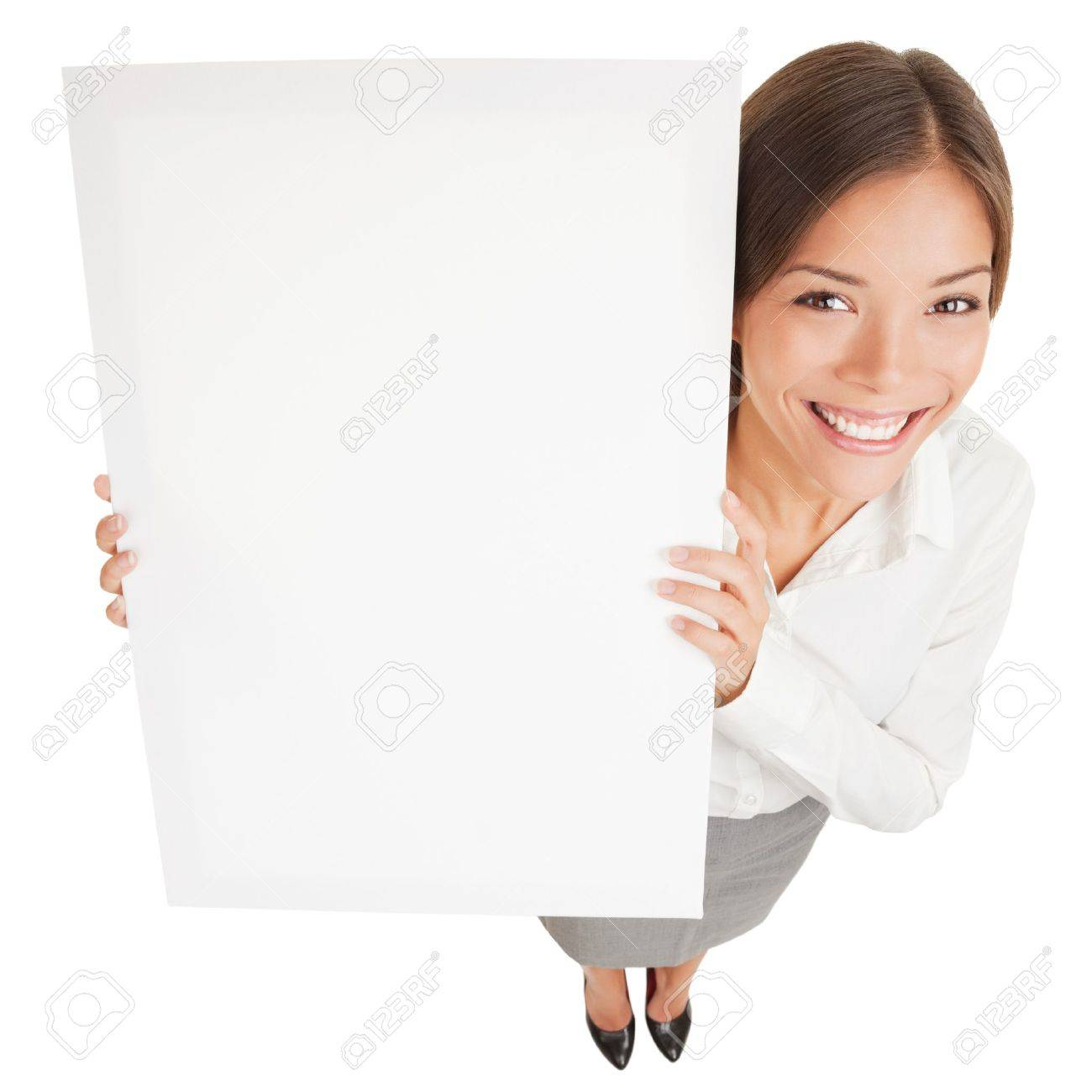 Woman showing a white board sign poster  High angle shot of attractive smiling woman with a blank white board isolated on white background  Mixed race Asian Caucasian business woman smiling happy Stock Photo - 17600789