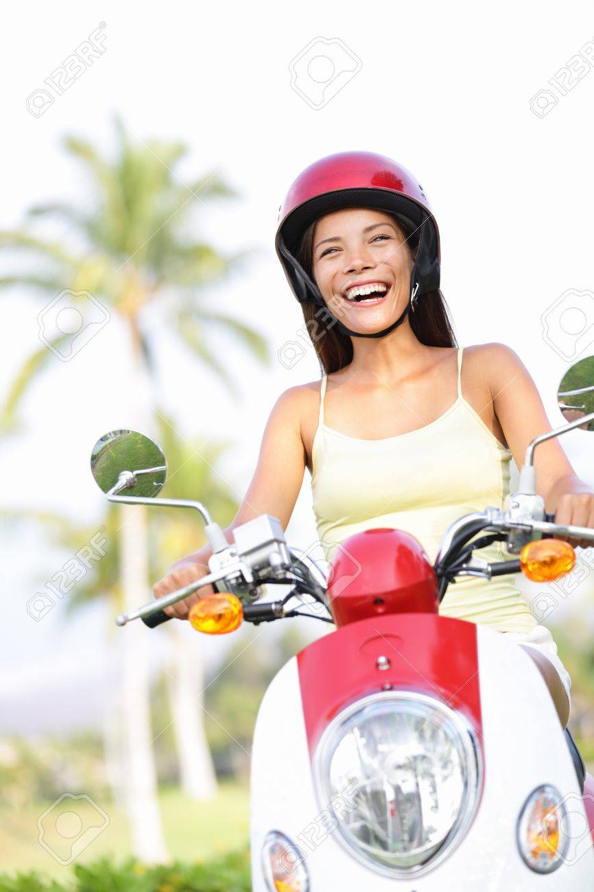 Free woman riding scooter happy. Beautiful asian woman joyful going on adventure riding scooter motorcycle on summer vacation holiday. Mixed race Asian Chinese / Caucasian girl. Stock Photo - 17699294