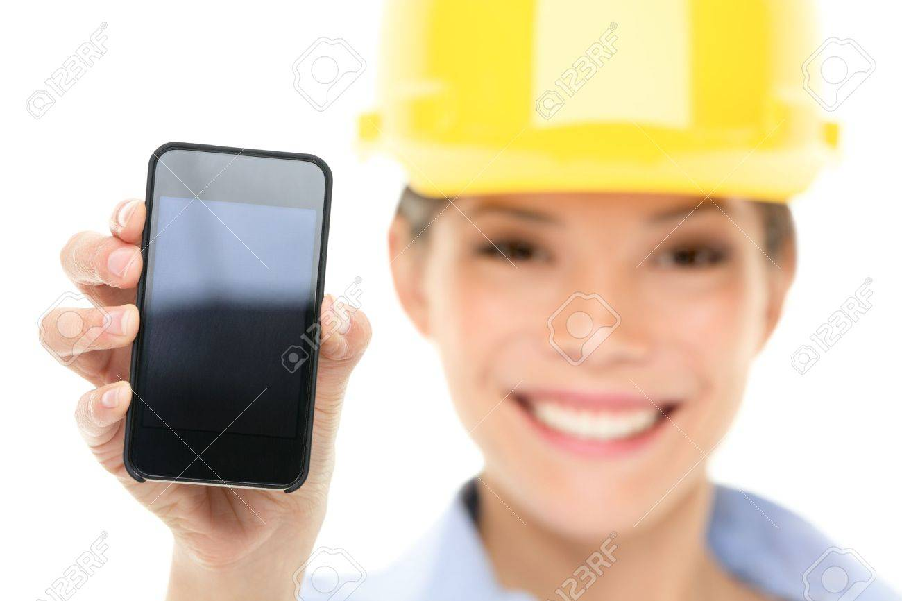 Engineer woman showing smart phone wearing construction hard hat. Young female mixed race Asian / Caucasian female professional isolated on white background. Stock Photo - 17718673