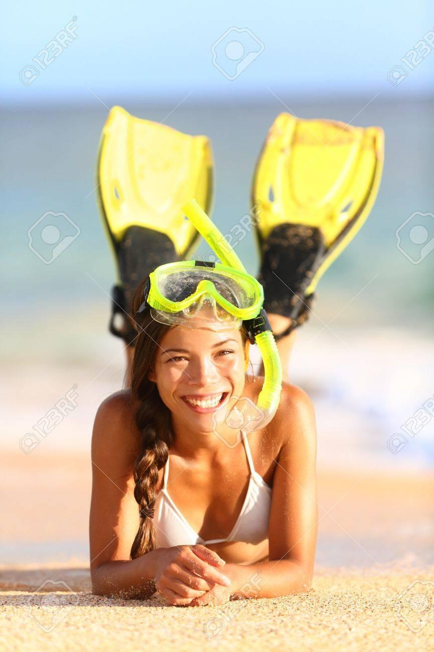 Beach holiday vacation woman snorkeling fun Joyful happy woman wearing snorkeling equipment, fins and mask, lying down in water and sand looking at camera Beautiful mixed race Caucasian Asian bikini model - 17924510