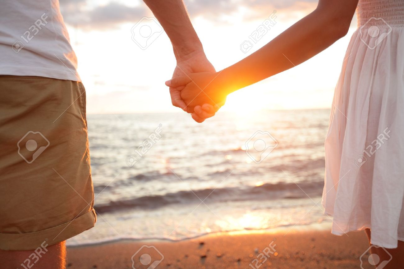 Summer couple holding hands at sunset on beach. Romantic young couple enjoying sun, sunshine, romance and love by the sea. Couple on summer vacation travel holiday. Stock Photo - 18730960